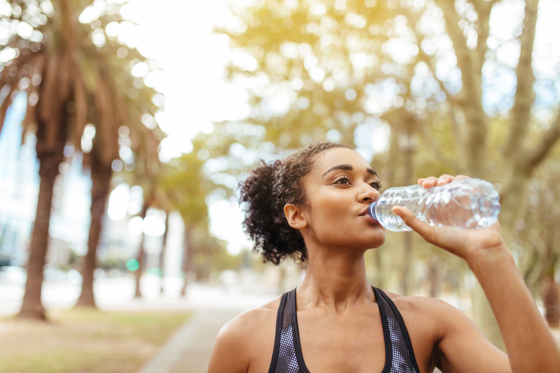 femme qui s'hydrate pendant son footing